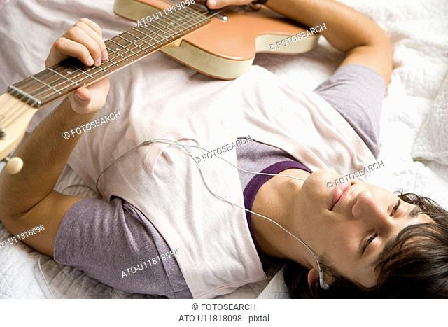 Young Japanese Man Playing Guitar with Listening to Music