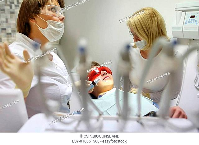 Doctor and nurse perform the procedure for dental treatment