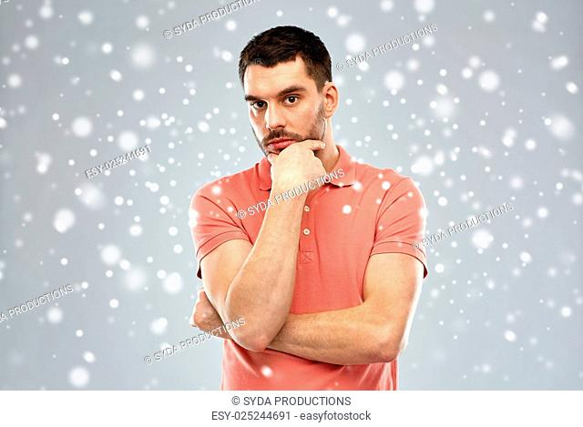 doubt, expression, winter, christmas and people concept - serious man thinking over snow on gray background