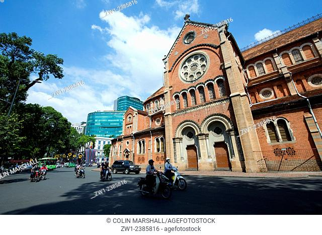 Motorbikes on road in front of Notre Dam Cathedral, Ho Chi Minh City (HCMC), Vietnam
