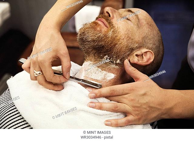 A customer sitting in the barber's chair, having his chin shaved by a barber using a cut throat razor