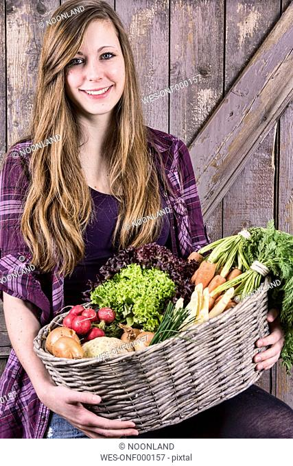 Germany, Portrait of teenage girl holding basket with organic vegetables, smiling