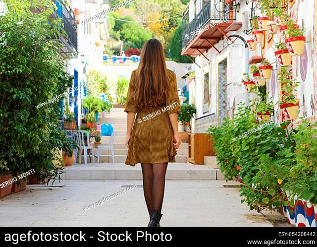Curious young woman walking in old street of Alicante, Spain. Rear view of happy cheerful girl visiting southern Europe