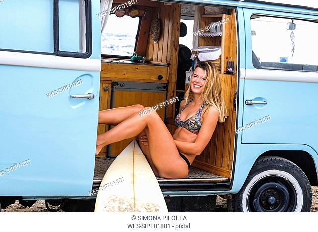 Portrait of happy young woman with surfboard in van