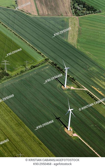Aerial view of a windfarm and wind turbines in the middle of agricultural farmland with green fields and electrical lines on poles, Lower Saxonia, Germany