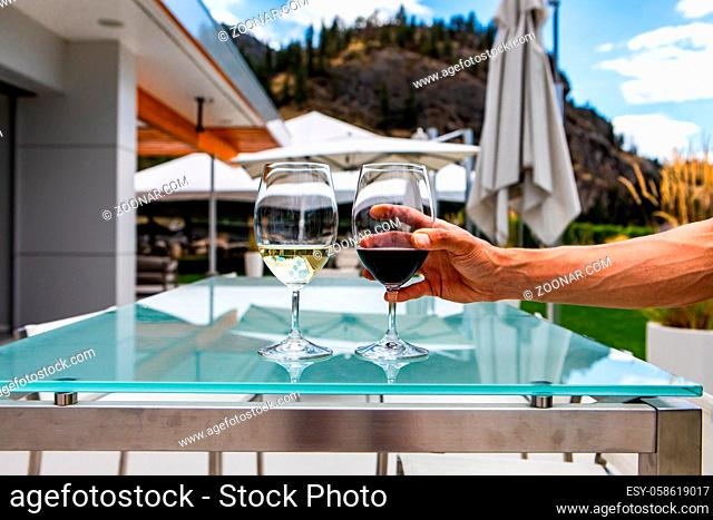 man hand on red wine glass on modern glass dining tables, pair of white and red wines glasses, outdoors the winery restaurant patio background