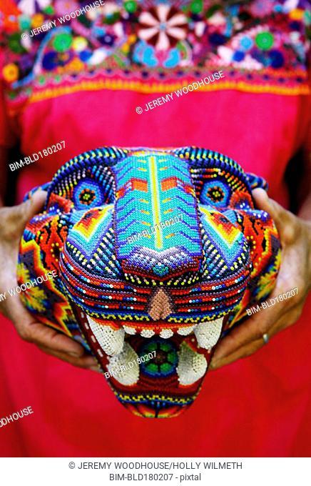 Caucasian artisan holding traditional beaded sculpture