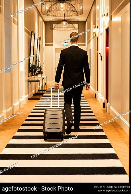 Anonymous businessman walking on striped carpet in hotel