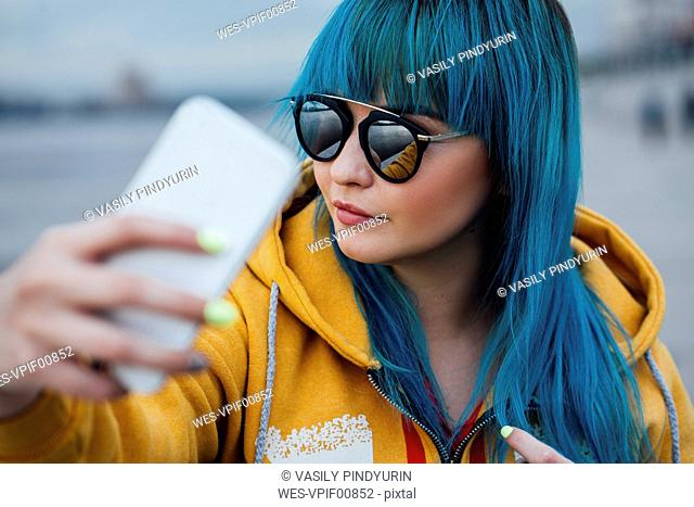 Portrait of young woman with dyed blue hair taking selfie with smartphone