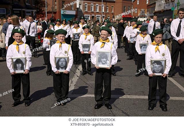 young children dressed in the uniform of the Fianna Eireann the IRAs junior wing carry photographs of dead Fianna members on Easter Sunday during the Easter...