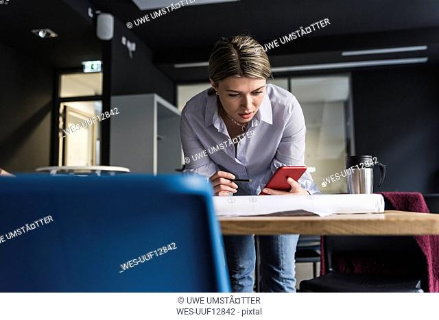 Young woman with cell phone and plan at table in office