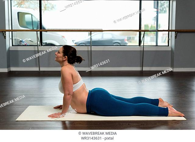 Pregnant woman exercising in living room