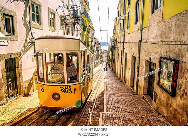 A small railway car, a funicular railway transport in a narrow street in a city. Lisbon, Portugal
