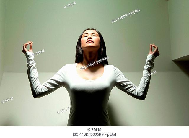 Woman meditating under spotlight