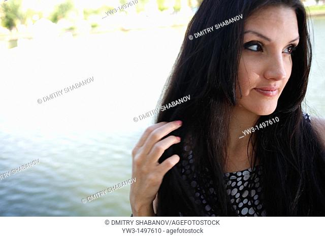 Cute face of 25 year old pretty woman outdoors near pond