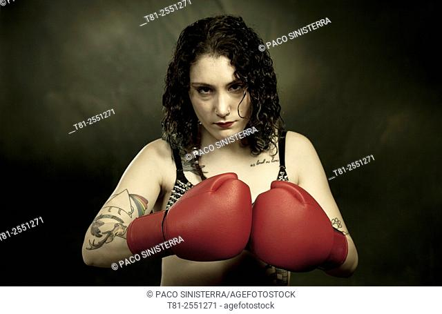 Portrait of tattooed girl with boxing gloves. In, Spain