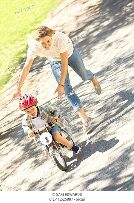 Mother pushing son with helmet on bicycle in sunny park