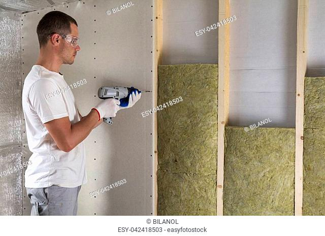 Worker in goggles with screwdriver working on insulation. Drywall on wall beams, insulating rock wool staff in wooden frame