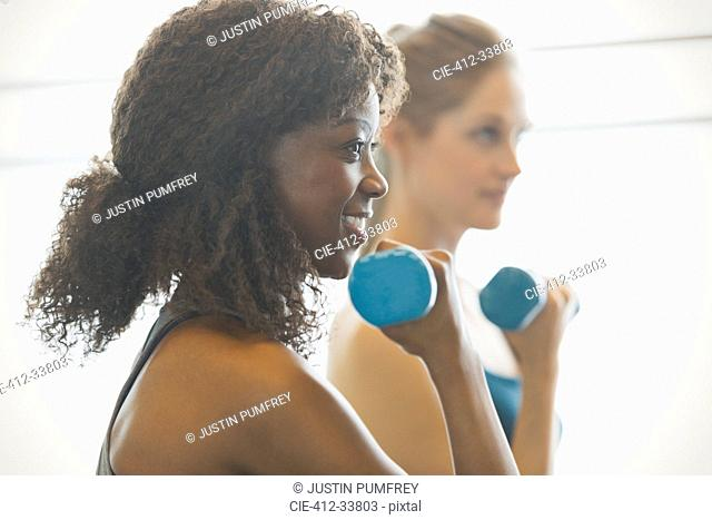 Smiling woman doing biceps curls in exercise class gym studio