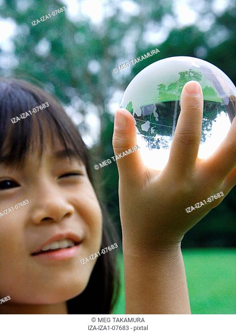 Close-up of a girl smiling and holding a globe