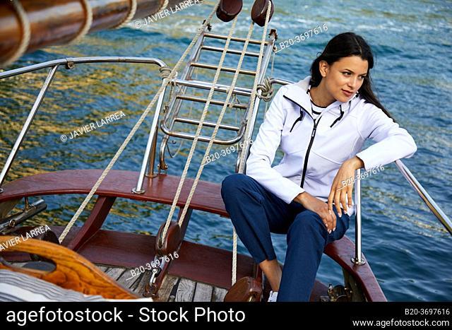Young woman with raincoat, Sailing boat, Pasaia port, Gipuzkoa, Basque Country, Spain, Europe