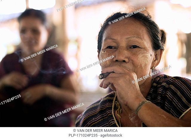 Old Burmese woman of the Bamar tribe wearing thanaka and smoking a cigar in Kayin village near Hpa-an, Kayin State / Karen State, Myanmar / Burma