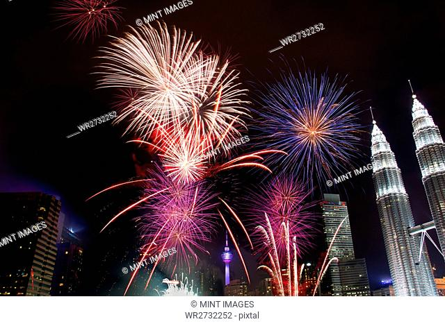 The Petronas Towers and the Asia City towers, of Kuala Lumpur at night, a firework display