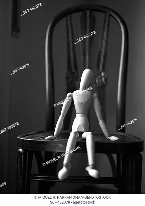 Wooden figure sitting on a chair in a fragility attitude