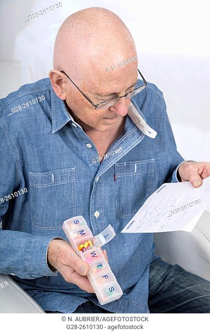 Senior man holding a prescription and a weekly pill organiser