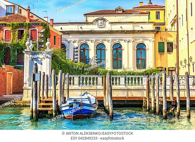 Grand Canal pier for gondolas and boats near an old palace of Venice, Italy