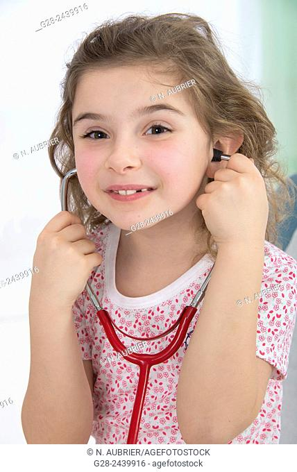 Little smiling girl sitting on a medical couch and listening to her heart with a stethoscope