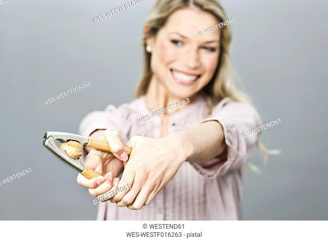 Mid adult woman cracking walnut with nut cracker