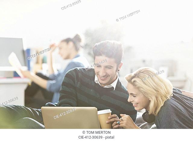 Young couple drinking coffee and using laptop