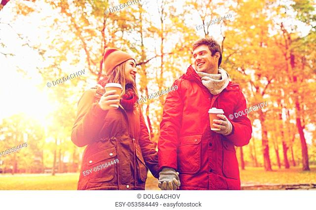 love, relationships, season and people concept - happy young couple with coffee cups walking in autumn park