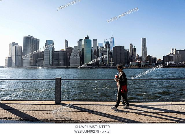 USA, Brooklyn, businesswoman looking at her smartphone in front of Manhattan skyline