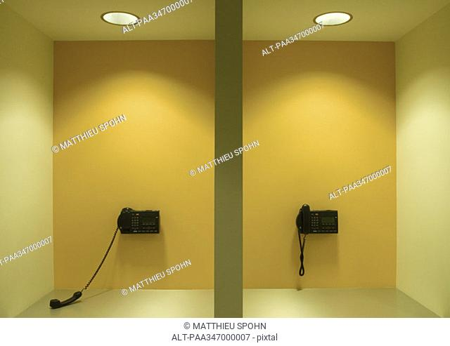 Two wall phones, one off the hook