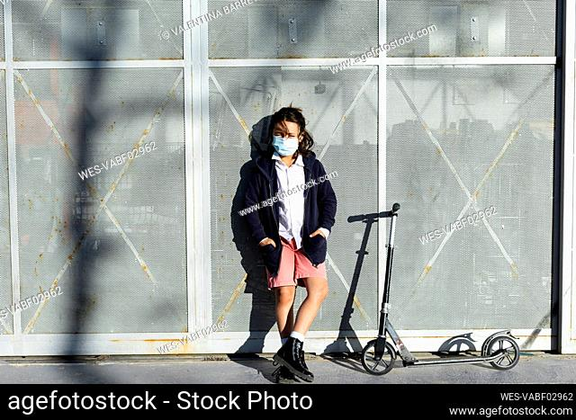 Portrait of boy wearing protective mask with scooter in the city