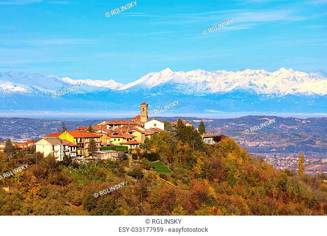 View of small town on top of the hill surrounded by autumnal trees and snowy peaks of Alps on background in Piedmont, Northern Italy