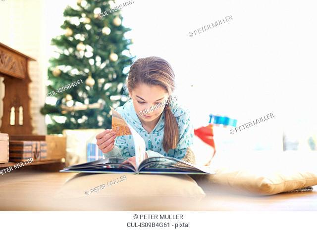 Girl lying on living room floor reading book at christmas