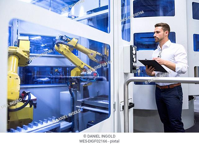Man taking notes at robotics machine in factory shop floor
