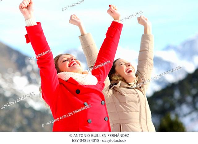 Two excited women raising arms with a snowy mountain in the background in winter