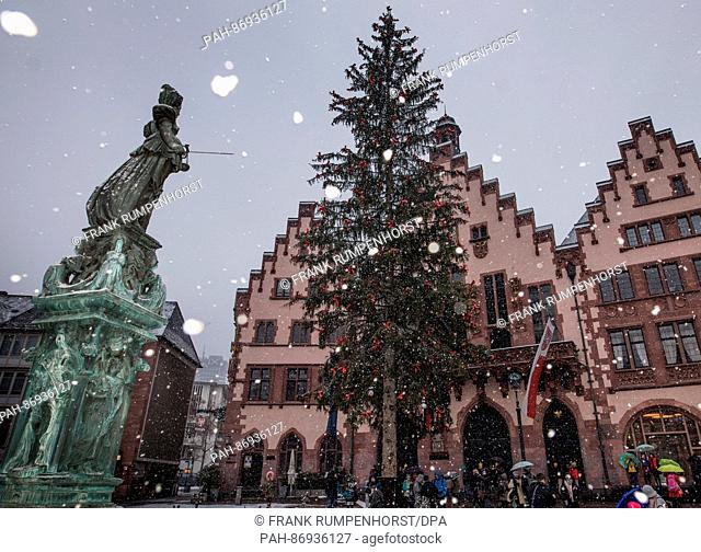 Snow is falling in front of the statue of Justitia (l) and the historical Roemer city hall at the Roemerberg, Frankfurt, Germany, 02 January 2016