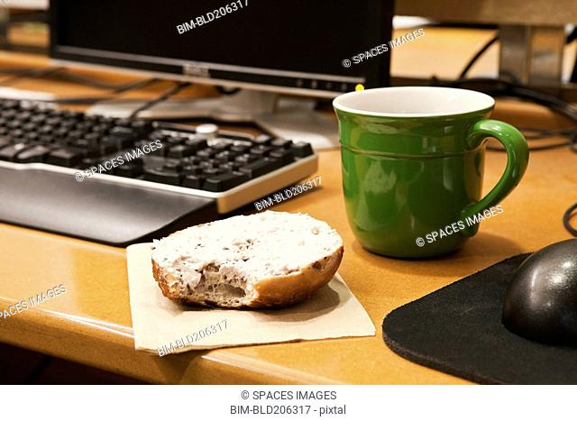 Coffee Cup and Bagel on a Desk