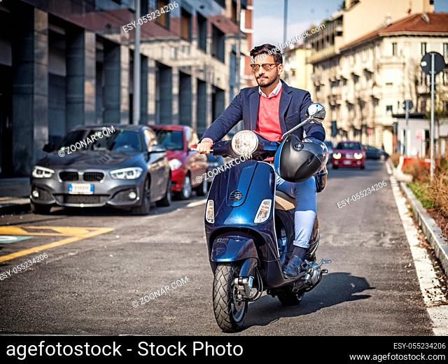 Young stylish man in suit and sunglasses driving scooter on empty road in sunny city