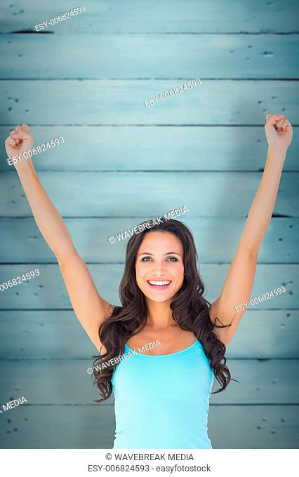 Composite image of casual brunette cheering at camera
