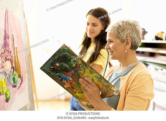 happy women painting at art school studio