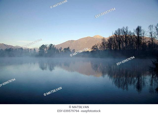 Mountain and trees reflected in a foggy lake with blue sky