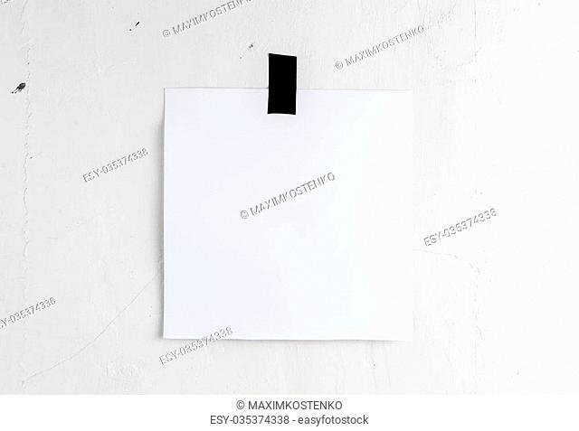 Blank white poster hanging on a tape on the wall. Template background for your design