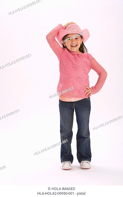 Studio portrait of young girl wearing pink cowgirl hat