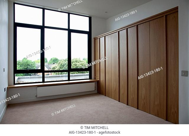 Small empty bedroom with folding storage in Modern Apartments, Hampton Wick